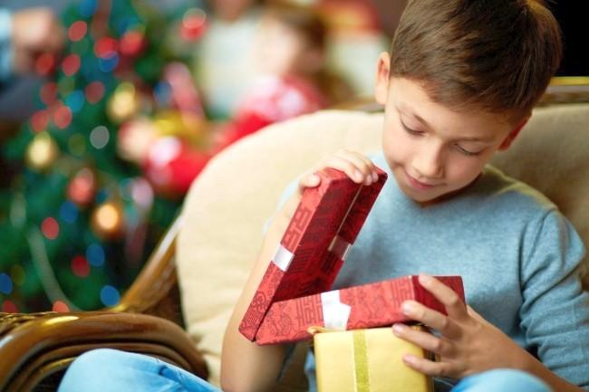 мальчик открывает новогодний подарок