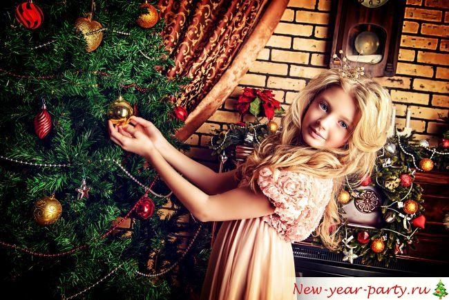 Красивая девочка наряжает елку